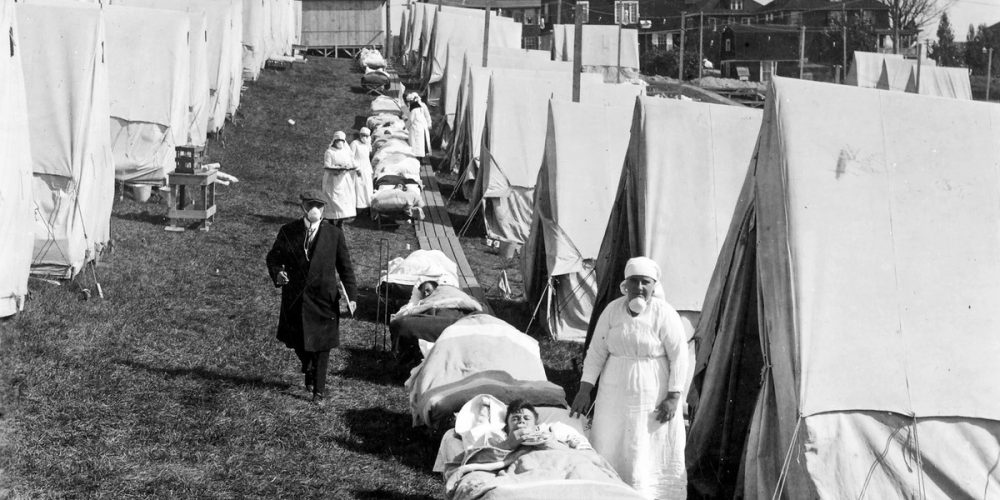 Influenza patients getting sunlight at the Camp Brooks emergency open-air hospital in Boston. Medical staff were not supposed to remove their masks. (National Archives)